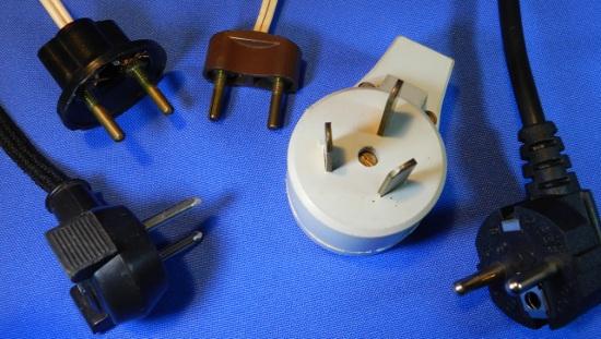 Figura 9 - Plugues incompatíveis com o novo padrão NBR de plugues e tomadas. Da esquerda para a direita: modelo de ferro de passar, de baquelite com e sem proteção, Nema 10 e Schuko.