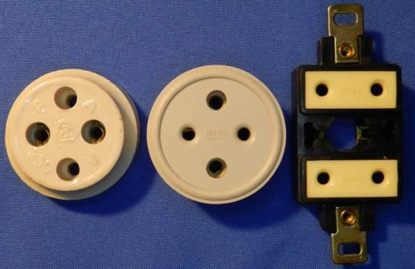 Figura 13 – Antigas tomadas de 2 pinos redondos, a da esquerda é de porcelana (louça) e as restantes são de baquelite.