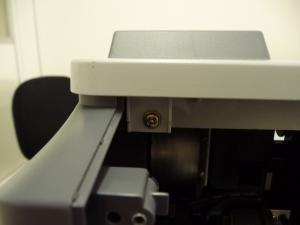Figura 14 – Parafuso traseiro da tampa superior, lado das teclas de comando.