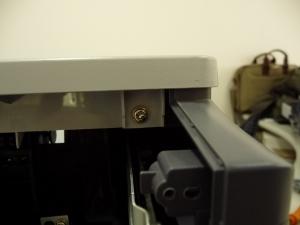 Figura 15 – Parafuso traseiro da tampa superior, lado oposto às teclas de comando.