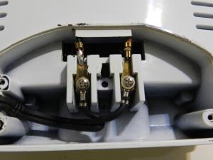 Figura 22 – Conexões da entrada de rede elétrica após as modificações. Pode-se notar que elas estão mais para dentro do que na figura 6, pois o parafuso que fixa cada conexão tem um furo na carcaça do aparelho, que o deixa imobilizado. No espaço livre para o fio terra pode-se ver tal orifício.