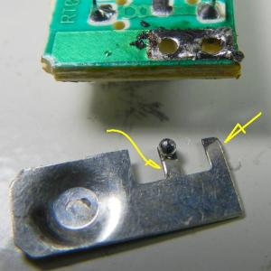 Figura 7 – Placa de contato da pilha, já retirada, onde as setas indicam que a solda original não estava bem espalhada nos pontos de ancoragem.