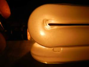Figura 91 – Lâmpada compacta NKT de 15W, de procedência desconhecida. O filamento da pequena lâmpada incandescente aparece através do bulbo.