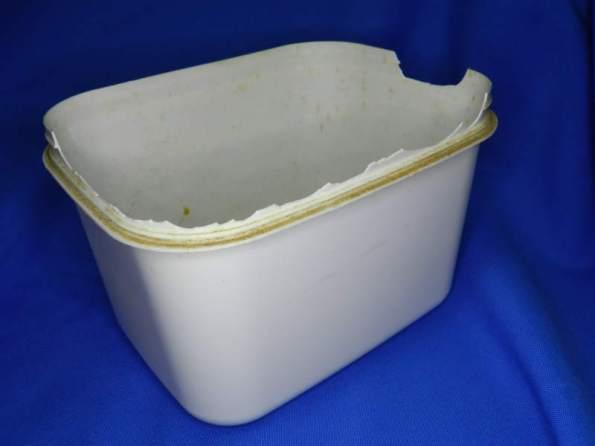 Figura 93 – Pote de sorvete, exposto alguns anos à uma lâmpada fluorescente. Num dos lados, o plástico ressecou e está esboroando. O lado intacto ficou mais protegido da luz.