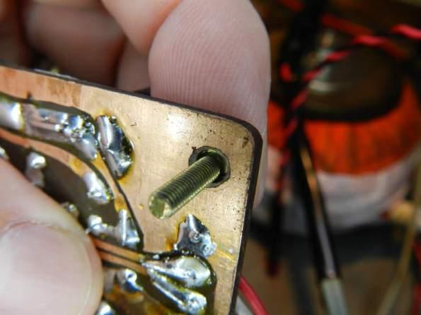 Figura 113 – Detalhe do furo da placa, com o parafuso utilizado para a montagem.