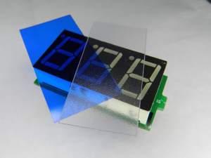 Figura 3 - Amperímetro desmontado, com película colorida, junto à lâmina difusora do amperímetro.