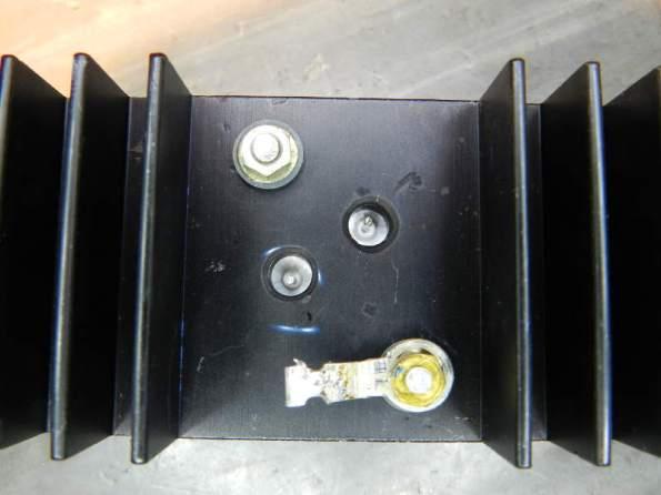 Figura 53 - Fixação do transistor TO-3 no dissipador, após o aperto dos parafusos. Observar que a pasta térmica vazou pelos furos da mica, junto dos terminais de base e emissor.