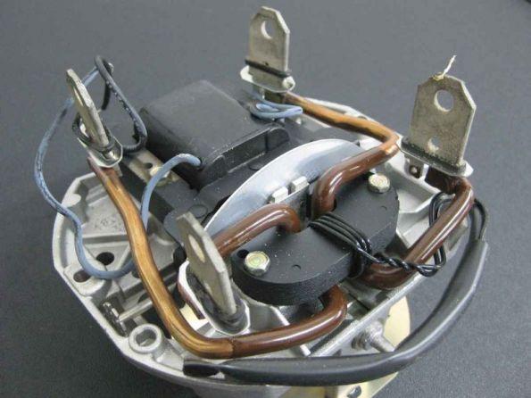Figura 60 – Motor do medidor removido do invólucro, deitado, onde aparecem a bobina de tensão (ao fundo) e as bobinas de corrente (fios grossos com terminais). Fonte: Popular Science [84].