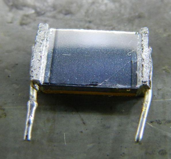 Figura 8 – Capacitor multicamadas aberto, em detalhe. Pode-se perceber a folha de filme plástico rasgada no canto inferior direito do capacitor, deixando aparecer a camada inferior.
