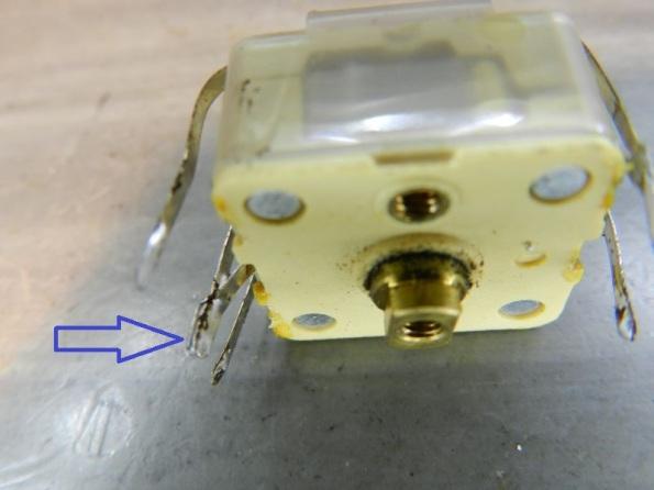 Figura 30 – O pino marcado pela seta deve ser dessoldado e separado para poder remover a capa. Alguns capacitores podem ter dois terminais superiores de aterramento, soldados na base.