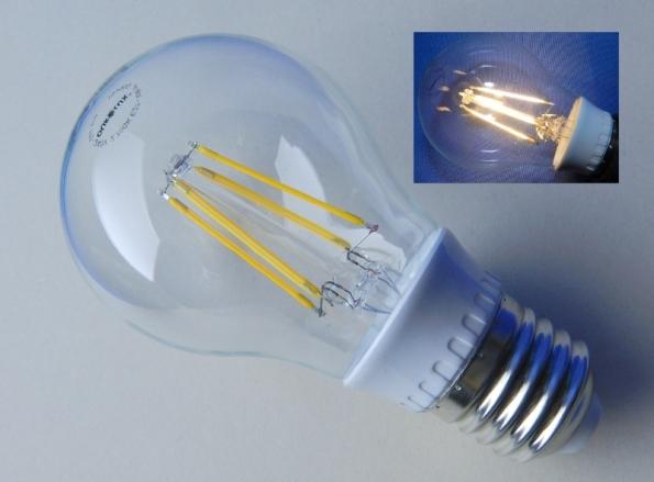Figura 1 – Lâmpada de filamento LED tamanho A60 vendida no Brasil, marca Ourolux, de 6W, bivolt, emissão de 600 lumens, 10 mil horas de vida útil, selo Procel A. No detalhe, a mesma lâmpada, ligada.