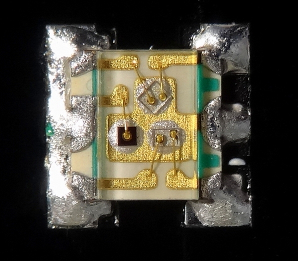 Figura 18 – LED RGB Everlight, de montagem em superfície (SMD), onde podem ser vistos os 3 chips soldados ao invólucro (dois do tipo LLED e um VLED (vermelho, que é o mais escuro deles)). Fonte: Wikimedia Commons [44].
