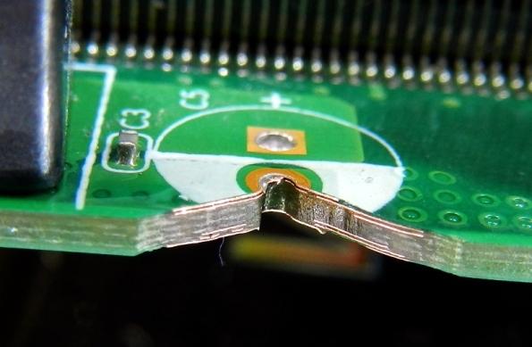 Figura 18 – Detalhe das camadas da placa mãe CCE, modelo PCI MBA 14HV0X PCHUSB+i5 2410M, junto a um capacitor. A parte de cobre do furo metalizado foi removida. É possível perceber as trilhas de cobre, em várias camadas internas.