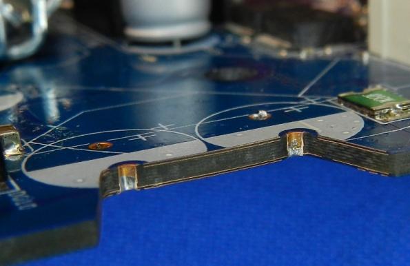 Figura 19 – Detalhe das camadas da placa mãe Gigabyte GA945GCM-S2C, junto a dois capacitores. Os furos metalizados estão preservados.