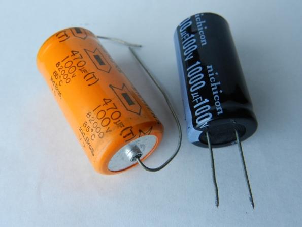Figura 31 – Capacitores eletrolíticos de alumínio tradicionais, o da esquerda é axial (terminais dispostos no eixo axial) e o da direita, radial (terminais dispostos em raios).