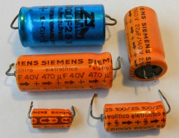 Figura 32 – Capacitores eletrolíticos úmidos da década de 1980, com indicação do polo positivo.