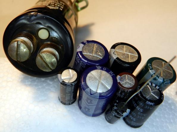 Figura 39 – Capacitores eletrolíticos úmidos de diversos tipos e tamanhos, onde é possível perceber as válvulas de proteção contra explosão.