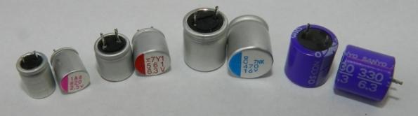 Figura 40 – Capacitores eletrolíticos de polímero condutivo sólido. Da esquerda para a direita: capacitor da FCE, linha RL, de 820uF/6,3V; Fujitsu FPCAP, de 560uF/6,3V; Nippon Chemi-con FPCAP, de 470uF/16V; Sony OS-CON, de 330uF/6,3V. Todos foram identificados pela página japonesa CapacitorWeb [15].