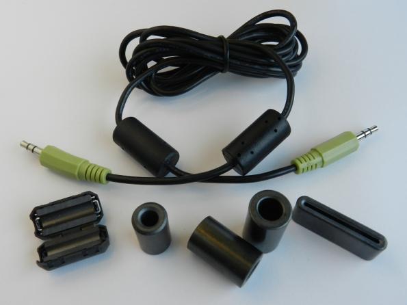 Figura 56 – Ferrites contra interferências de RF. O cabo com plugues P2 estéreo tem dois ferrites moldados nas extremidades, originais. O ferrite abaixo, à esquerda, pode ser montado no cabo pronto, ao contrário dos outros.
