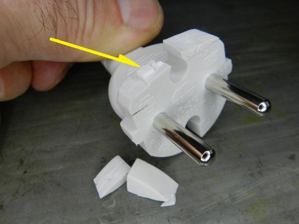 Figura 24 – A seta mostra o plástico rígido que forma o esqueleto interno do plugue CEE 7/17. Não foi possível cortá-lo, era muito duro para o estilete, poderia quebrar a lâmina. Daí...