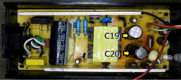 Figura 7 – Localização dos capacitores C19 e C20 na fonte compatível. Junto deles é possível perceber que a placa ficou mais escurecida, devido ao aquecimento.