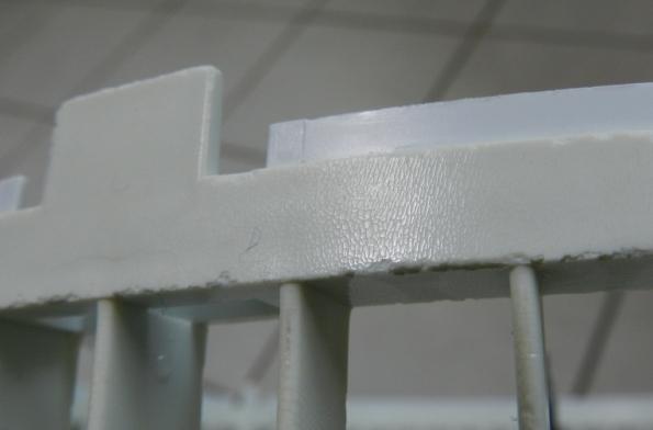 Figura 46 – Detalhe da grade traseira de um ventilador de mesa. Pode-se ver que a parte exposta à luz está craquelada e mais amarelada, diferente da parte coberta pela grade frontal (é a mesma peça plástica).