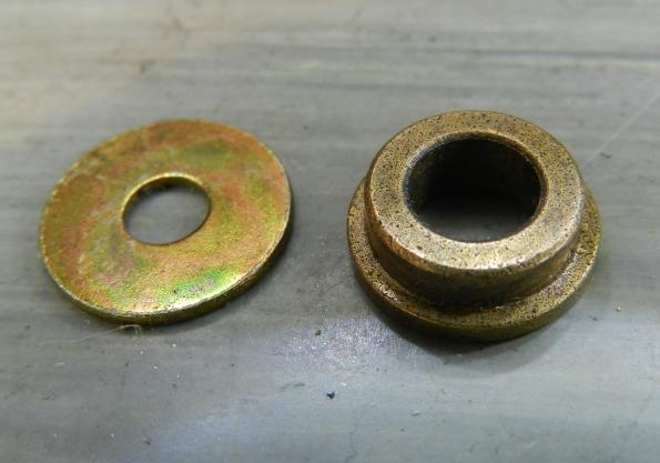 Figura 9 – Detalhe da bucha sinterizada (peça à direita), junto com uma arruela de latão. Observe que a bucha é toda pigmentada, são os poros do material.