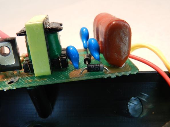Fig. 16 – Vista ampliada do circuito de alta tensão de uma raquete mata-mosquitos, onde é possível perceber a película de cera sobre os componentes.