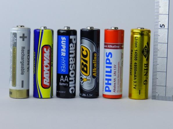Fig. 8 – Todas essas pilhas são do mesmo tamanho (AA, xR6 ou 14500).  Começando da esquerda para a direita, temos uma Sony de NiMH e 1,2V; as comuns Rayovac e Panasonic e as alcalinas Bic e Philips são de 1,5V; e a de lítio (marca BIN'G), junto do esquadro, entrega 3,7V.