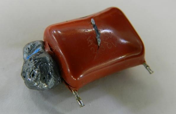 Fig. 8 – Capacitor de entrada C1 da lanterna recarregável, observe que o conteúdo fundiu-se e vazou para fora do encapsulamento.