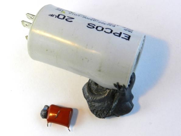 Fig. 9 – Capacitor da figura anterior junto a outro maior, ambos com o mesmo problema (extravasamento de conteúdo). Este último é utilizado em aparelhos de ar condicionado, para dar partida no motor do compressor.