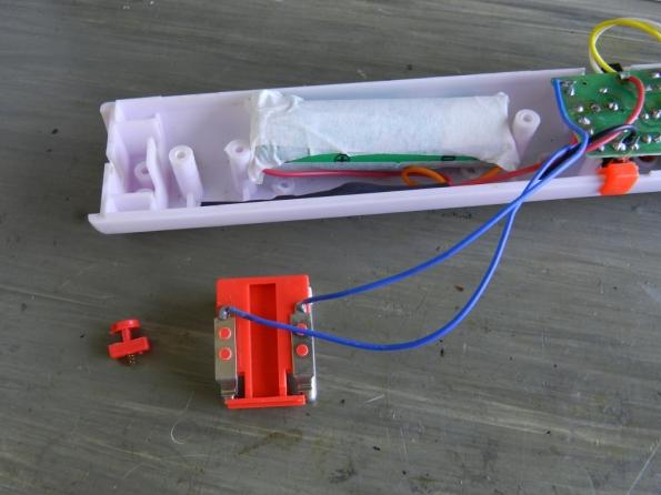 Fig. 13 – Pilha de lítio e circuito de controle, acomodados no cabo da raquete. Observe os frágeis fios azuis que vão do plugue retrátil da rede elétrica à placa.
